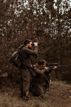 Two Hunters Are Hunting In The Forest, One Hunter Is Kneeling And Aiming, Another Hunter Is Standing Nearby And Looks Through Binoculars, Brown Tinted, Soft Focus, There Is A Little Creative Noise In