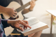 A Young Boy Sat And Read The Bible While His Friend Played Guitar At Church When He Worshiped God. A Small Group Of Christians Or A Concept In A Church At A Church