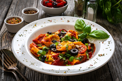 Tortelloni stuffed with prosciutto ham and vegetables on wooden table