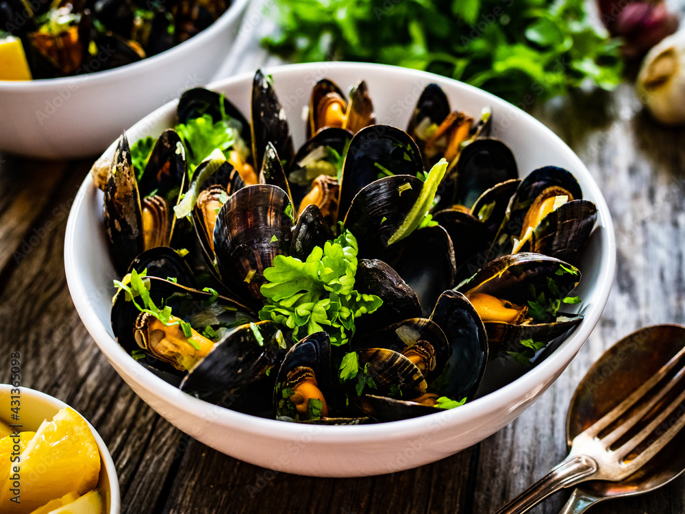 Obraz Cooked mussels with lemon and parsley on wooden table  fototapeta, plakat