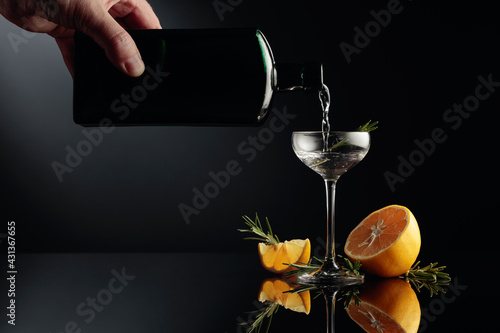 Gin with lemon and rosemary on a black reflective background. - fototapety na wymiar
