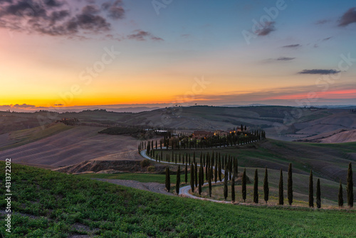 Fototapeta premium Tuscany, rural landscape at sunset. Rural farm, cypresses, green field, sunshine and clouds. Italy, Europe.