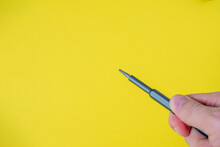 A Man's Hand Holds A Small Screwdriver With A Torx Nozzle On A Bright Yellow Background. Copy Space, Space For Text