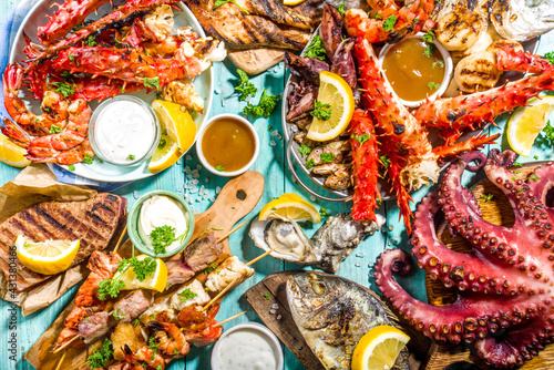 Assortment various barbecue Mediterranean grill food - fish, octopus, shrimp, crab, seafood, mussels, summer diet bbq party fest, with kebab, sauces, light blue sunny wooden background - fototapety na wymiar