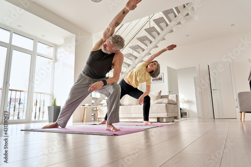 Fit middle aged 50s family couple doing fitness yoga morning exercise at home. Sporty healthy old mature man and woman training together standing in living room. Active seniors sport stretching. - fototapety na wymiar