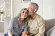 Leinwandbild Motiv Happy affectionate classy older mature couple bonding with eyes closed at home. Loving caring senior 50s husband embracing and kissing mid aged wife enjoying tender moment sitting on couch at home.