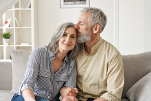 Happy Affectionate Classy Older Mature Couple Bonding With Eyes Closed At Home. Loving Caring Senior 50s Husband Embracing And Kissing Mid Aged Wife Enjoying Tender Moment Sitting On Couch At Home.