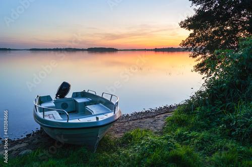 Fototapeta Masurian lake, sunset, motor boat