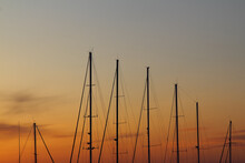Fiery Contrasting Clouds In The Blue Sky, At Sunset, Through The Masts Of Sailing Yachts.
