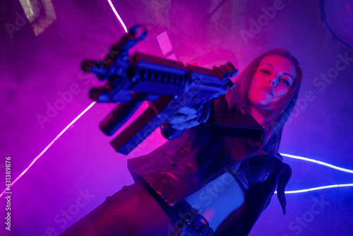 Stampa su Tela Cyberpunk girl with a rifle in the neon lights.