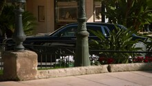 Tracking A Luxury Rolls Royce Car As It Pulls Up To The Casino, With Bright Sunlight, Walkways, And Security Guards - Monte Carlo, Monaco