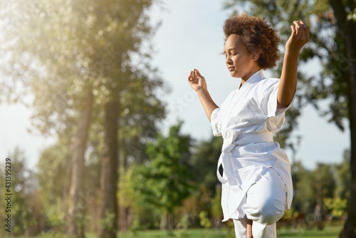 Serene Afro American girl in kimono meditating outdoors - fototapety na wymiar