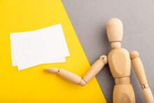 Wooden Mannequin Holding White Blank Poster On Gray And Yellow Pastel Background. Copy Space.