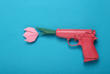 Origami Flower From The Barrel Of A Pink Gun On A Blue Background. Creative Romantic Concept. Minimalism Love Flat Lay. Minimal Layout.Top View