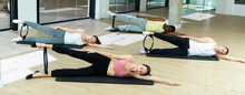 Portrait Of Concentrated Girl Performing Set Of Pilates Exercises With Magic Ring During Group Class In Fitness Studio