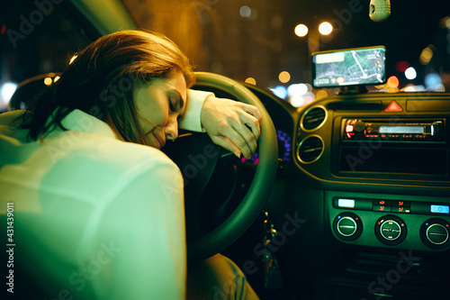 Sad woman crying behind steering wheel in a car at night. Fotobehang