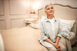 Leinwandbild Motiv People, rest, relaxation and fatigue concept. Beautiful short haired Caucasian woman wearing comfy casual clothes sitting on double size bed in cozy beige bedroom, having relaxed facial expression
