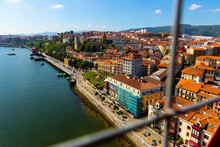 Portugalete From Vizcaya Bridge. Picturesque Modern Cityscape On Bank Of Nervion River With Ancient Basilica De Santa Maria, Spain..