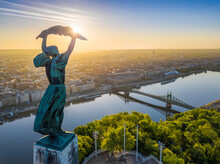 Budapest, Hungary - Aerial View From The Top Of Gellert Hill With Statue Of Liberty, Liberty Bridge And Skyline Of Budapest At Sunrise With Clear Blue Sky
