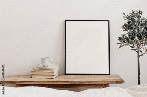 Vertical black picture frame mockup on vintage bench, table. Cup of coffee on pile of books. Potted olive tree. White wall background. Scandinavian interior, neutral color palette. Selective focus. - fototapety na wymiar