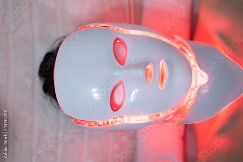 Obraz Woman with led light therapy facial and neck beauty mask photon therapy. Home skincare and me time concept - fototapety do salonu