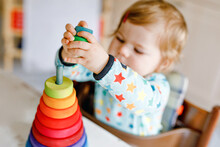 Cute Beautiful Little Baby Girl Playing With Educational Toys At Home Or Nursery, Indoors. Happy Healthy Child Having Fun With Colorful Wooden Rainbow Toy Pyramid. Kid Learning Different Skills.