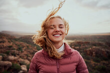 Smiling Young Confident Woman With Closed Eyes Feeling Fresh Wind Against Face Standing On Mountain Hill