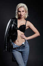 Studio Fashion: Cute Young Woman In Black Leather Jacket, Brassiere And Blue Jeans. Seductive Informal (rock) Girl Against Gray Background