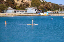 A Woman Standing On A Paddle Board Near Orange And White Buoys On Deep Blue Ocean Water With Boats And Yachts Docked In The Harbor At Baby Beach In Dana Point California