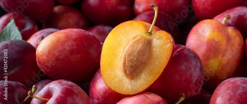 Fotografie, Obraz Ripe red plums, fruit background close up. Banner.