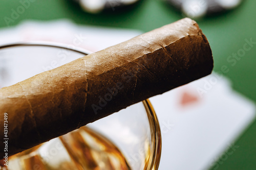 Obraz Close up of whiskey glass and cigar on green background - fototapety do salonu