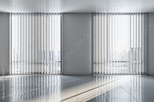Fototapeta Sunny spacious empty room with ceramic tiles floor and city view from blinds on big windows obraz