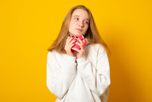 Cute Teen Girl Wearing A White Hoodie Warms On A Hot Cup Of Tea. Young Girl In Autumn Hoodie Drinking From A Colorful Mug.