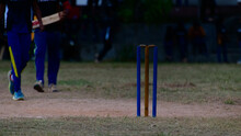 Softball Cricket Match In The Village, After Sundown Evening Darkness. Isolated Pitch And Wooden Wickets.
