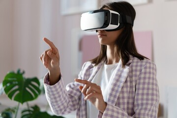 Confident young woman in virtual reality headset pointing in the air while standing at her working place in office