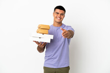 Young Handsome Man Holding Pizzas And Burgers Over Isolated White Background Shaking Hands For Closing A Good Deal