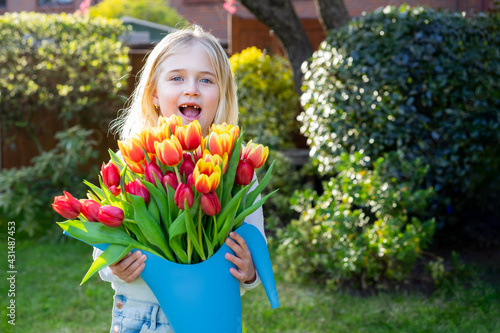Photo Cute adorable smiling toothless little girl with a huge bunch of tulips in the watering can