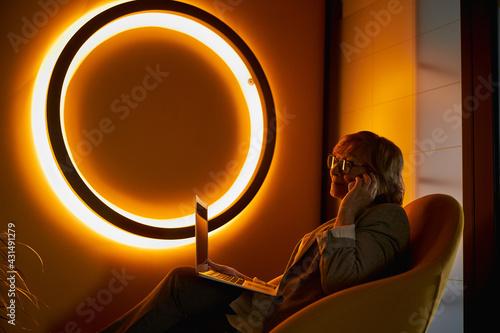 Fototapeta Senior citizen talking on phone near orange neon sign obraz