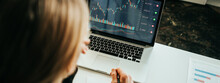 Woman Working With Investment Stock Market Using Laptop, Analyzing Trading Data