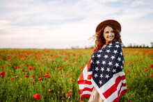 Young Woman In Hat With The American Flag In In The Poppy Field. Fourth Of July. Freedom. Beautiful Sunset. Independence Day. Patriotic Holiday.