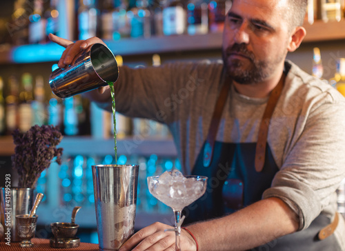 Obraz Barman gently pouring beer into shaker on bar counter - fototapety do salonu