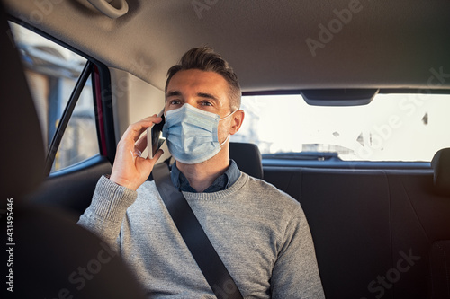 Canvas Businessman sitting in a taxi while talking over phone with mask