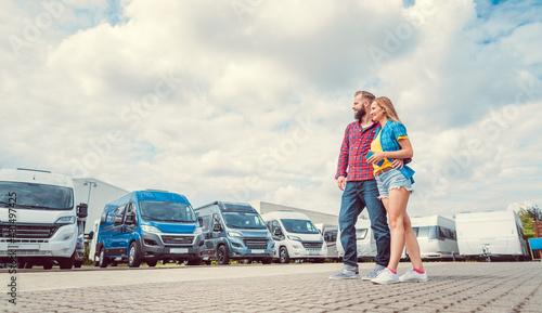 Naklejka premium Woman and man choosing camper van to rent or buy