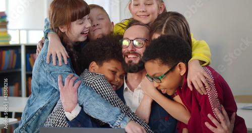 Valokuvatapetti Interracial kids hugging happy teacher at table in classroom