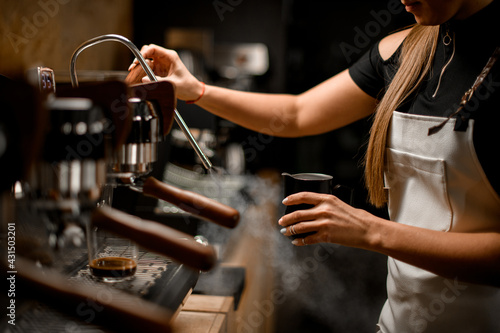 Papel de parede female barista turns on coffee machine that releases steam to make coffee drink
