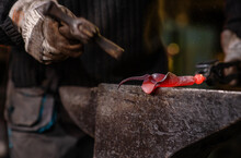 A Close-up Image Of A Blacksmith's Hands Forging A Jewelry Flower From A Hot Sheet Of Metal. Manual Rework In The Forge Concept