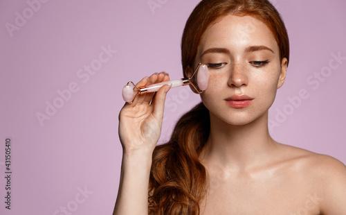 Fényképezés Redhead beauty girl massage facial healthy glowing skin with pink quarz roller,