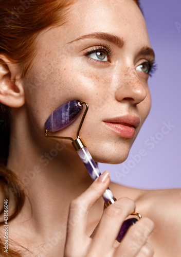 Obraz Close up of beauty redhead use natural jade face roller on cheek, massaging facial muscles, lifting, healthy glowing result. Girl doing spa skin care procedures, penetrates cream with quarz tool - fototapety do salonu