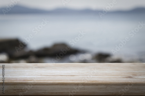 Fototapeta Closeup of a wooden surface with copyspace with the sea on the blurred background obraz