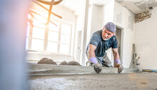 Filling The Floor Of A Renovated Apartment With Concrete, Screed And Leveling The Floor By Construction Workers. Even Floors Made Of A Mixture Of Cement, Industrial Concreting. Bright Sun Shine